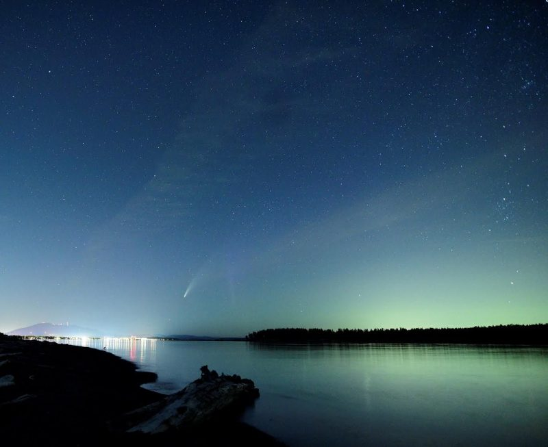 Comet and aurora against a starry medium blue sky, over a body of water.