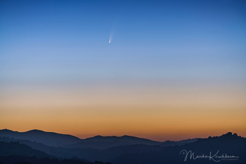A comet with a split tail set against a bright twilight sky over blue hills.