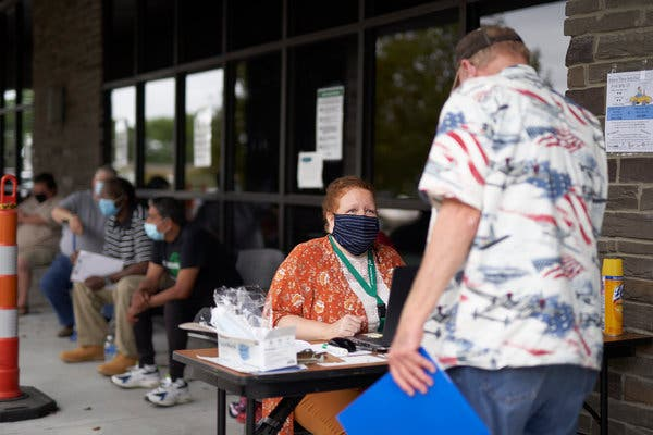 A representative of Heartland Workforce Solutions, which connects job seekers with regional employers, talking with an applicant outside the organization's office in Omaha on Wednesday.