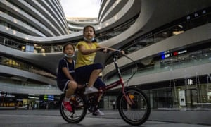 Two children ride a bike at a shopping mall in Beijing, China on 19 July 2020.