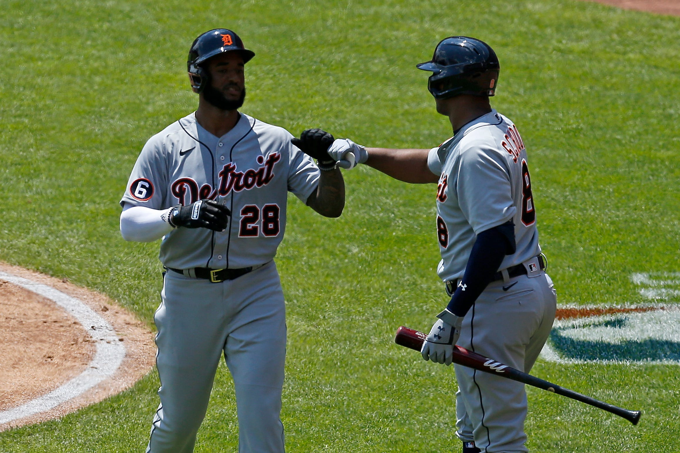 Detroit Tigers shortstop Niko Goodrum (28) fist bumps with second baseman Jonathan Schoop after a solo home run in the third inning vs. the Cincinnati Reds at Great American Ball Park in Cincinnati on Sunday, July 26, 2020.
