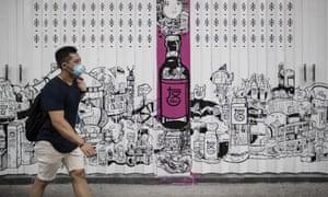 A man wearing a face mask as a preventive measure against coronavirus walks past a closed bar in Hong Kong.