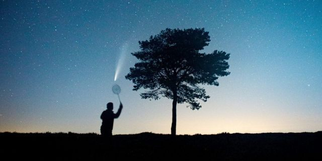 This stunning picture shows a man pretending to play badminton with Comet NEOWISE above the Quantock Hills in Somerset. (Credit: SWNS)