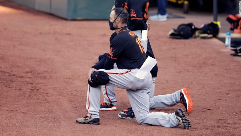San Francisco Giants' players and manager kneel during national anthem in exhibition game against Oakland