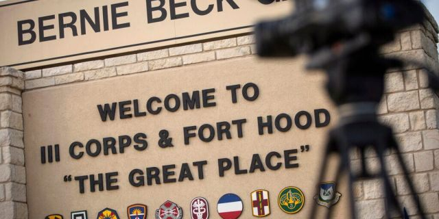 FILE: Members of the media wait outside of the Bernie Beck Gate, an entrance to the Fort Hood military base in Fort Hood, Texas.