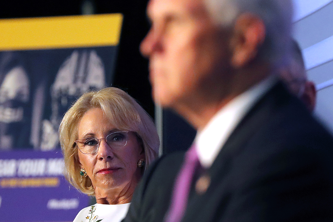 Education Secretary Betsy DeVos listens as Vice President Mike Pence speaks | AP Photo